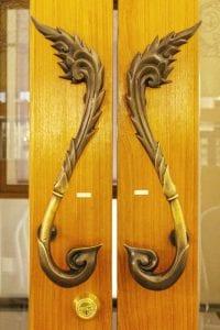 Door handle on wooden and glass door, Thai style.
