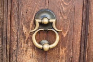 Vintage style retro bronze door handle or knocker with wooden door.